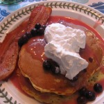Orange-Blueberry Pancakes with Orange-Blueberry Sauce, Whipped Cream, and Bacon
