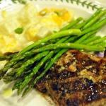 Peppered Ribeye Steaks with Truffle Vinaigrette, Roasted Asparagus, and Potatoes Romanoff